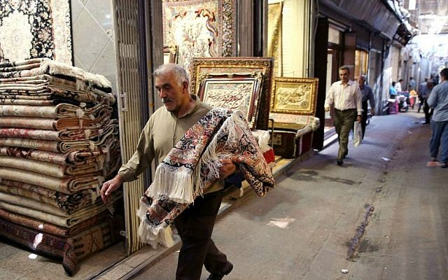 In this Monday, Aug. 10, 2015 photo, an Iranian man carries a carpet through Tehran's old main bazaar, Iran. (AP Photo/Vahid Salemi)