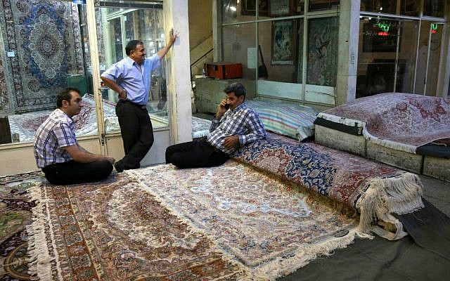 In this Monday, Aug. 10, 2015 photo, Iranian merchants wait for customers at a carpet market in Tehran's old main bazaar, Iran. (AP Photo/Vahid Salemi)