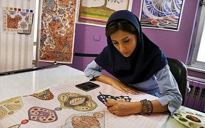 In this Tuesday, Aug. 4, 2015 photo, an Iranian woman sketches and paints carpet patterns at a workshop in the Cultural and Artistic Carpet Foundation of Rassam Arabzadeh in Tehran, Iran. (AP Photo/Vahid Salemi)