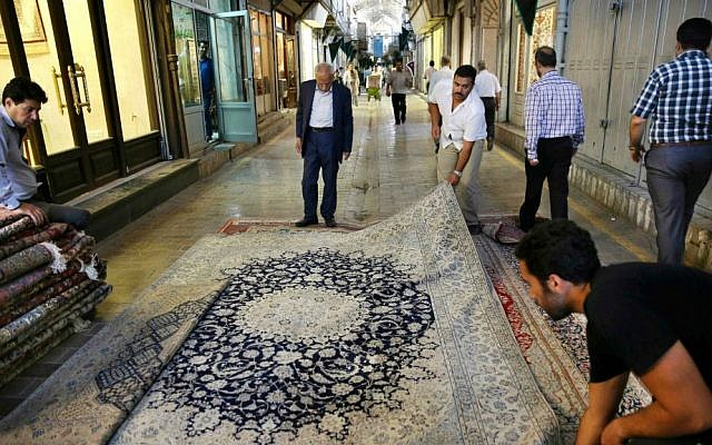 In this Monday, Aug. 10, 2015 photo, Iranian merchants display a carpet at the Tehran's old main bazaar, Iran. (AP Photo/Vahid Salemi)