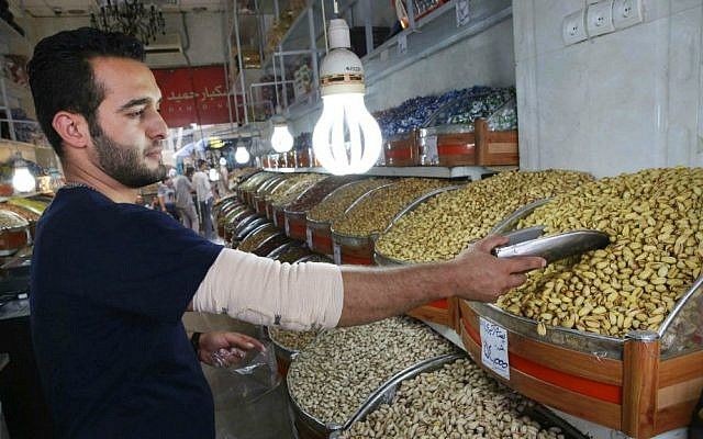 In this Monday, Aug. 10, 2015 photo, Iranian shopkeeper Emad Abri poses for a photograph next to pistachios he hopes to sell, in his shop at Tehran's old main bazaar, Iran. (AP Photo/Vahid Salemi)