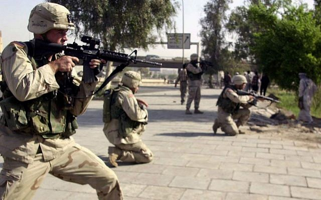 In this Oct. 4, 2003 file photo, American soldiers aim towards a stone-throwing mob of ex-Iraqi soldiers near a former military airport in central Baghdad, Iraq. (AP Photo/Khalid Mohammed, File)