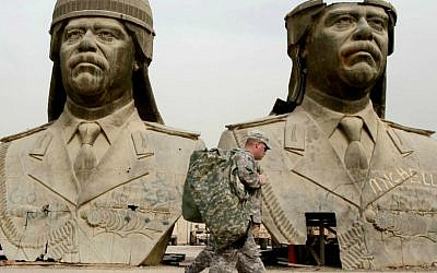 In this March 20, 2009, file photo, US Army soldiers stroll past two bronze busts of former Iraqi President Saddam Hussein in the Green Zone in Baghdad, Iraq. (AP Photo/Hadi Mizban, File)