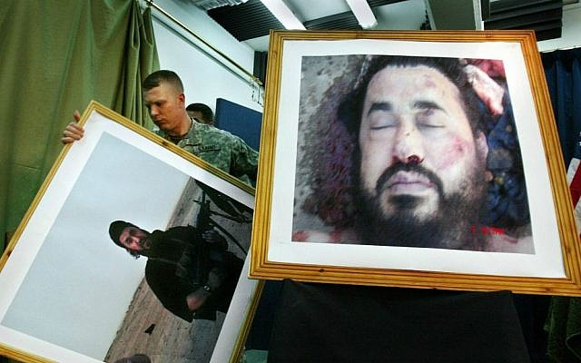In this June 8, 2008, file photo, a US soldier at a press conference in Baghdad, Iraq, takes down an older photo, to display a new image purporting to show the body of Abu Musab al-Zarqawi, an al-Qaeda-linked militant who led a bloody campaign of suicide bombings, kidnappings and hostage beheadings in Iraq. (AP Photo/Khalid Mohammed, File)