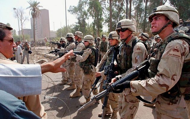 US soldiers prevent former Iraqi soldiers from trying to enter the American headquarters during a deadly demonstration in Baghdad, Iraq, on June 18, 2003. (AP Photo/Victor R. Caivano, File)