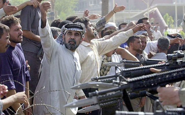 In this June 18, 2003 file photo, US soldiers, partly seen at right, prevent former Iraqi soldiers from trying to enter the American headquarters during a deadly demonstration in Baghdad. (AP Photo/Victor R. Caivano, File)
