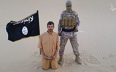 This image made from a militant video posted on a social media site on Wednesday, August 5, 2015, which has been verified and is consistent with other AP reporting, purports to show a militant standing next to another man who identifies himself as 30-year-old Tomislav Salopek, kneeling down as he reads a message at an unknown location. (Screen capture via AP)
