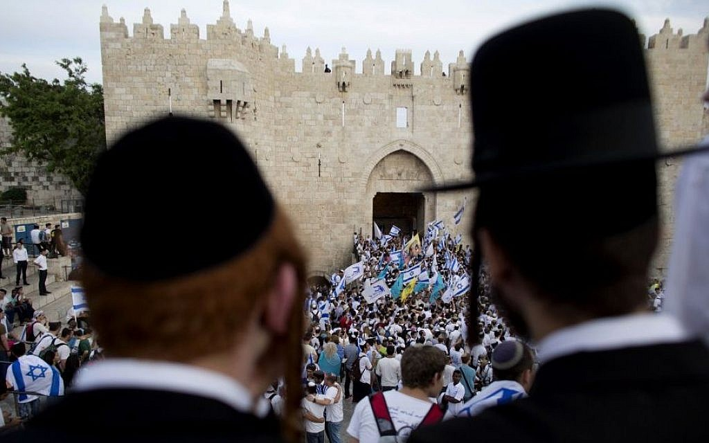 In this May 28, 2014, file photo, ultra-Orthodox Jews watch people wave Israeli flags outside the Old City's Damascus Gate during Jerusalem Day celebrations in Jerusalem. (AP Photo/Dusan Vranic, File)