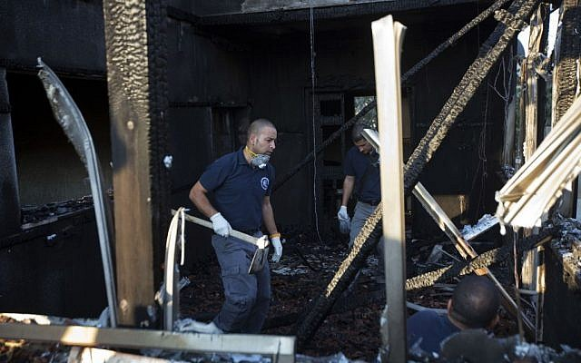 Israeli policemen inspect a house after it was torched in a suspected attack by Jewish terrorists killing an 18-month-old Palestinian child, at Duma village near the West Bank city of Nablus, Friday, July 31, 2015. (AP Photo/Majdi Mohammed)