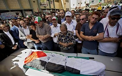 Palestinians prays by the body of Saad Dawabsha, 32, during his funeral procession in the West Bank village of Duma near Nablus on Saturday, Aug. 8, 2015. (AP Photo/Majdi Mohammed)