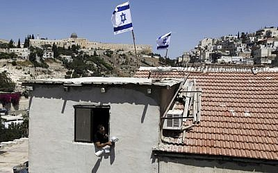 A man looks out of a window of building where Israeli flags fly from the roof, in the Silwan neighborhood of East Jerusalem on August 27, 2015. (AP Photo/Mahmoud Illean)