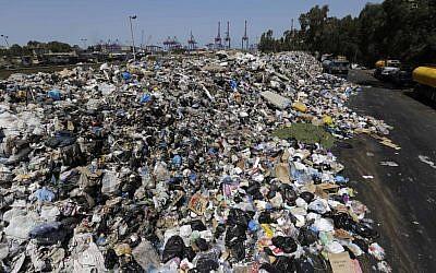 Piles of garbage blocks a street in east Beirut, Lebanon, Monday, Aug. 17, 2015. (AP Photo/Hassan Ammar)