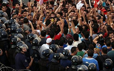 Activists chant slogans as Lebanese riot policemen stand guard in front the government house during a protest against the ongoing trash crisis, in downtown Beirut, Lebanon, Saturday, August 22, 2015. (AP/Bilal Hussein)
