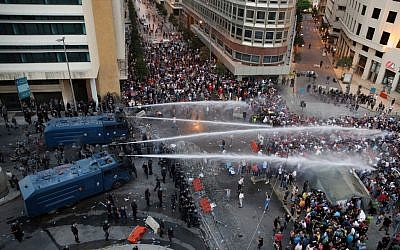 Lebanese activists shout anti-government slogans as they are sprayed by riot police using water cannons during a protest against the ongoing trash crisis, in downtown Beirut, Lebanon, Sunday, Aug. 23, 2015.  (AP Photo/Bilal Hussein)