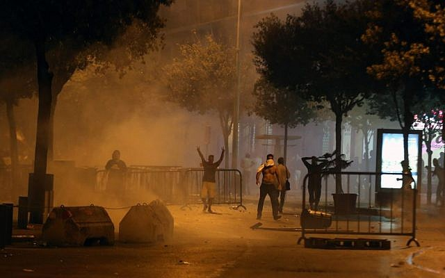 Demonstrators gesture as Lebanese riot police use tear gas during a protest against the ongoing trash crisis, in downtown Beirut, Lebanon, Saturday, August 22, 2015. (AP/Bilal Hussein)
