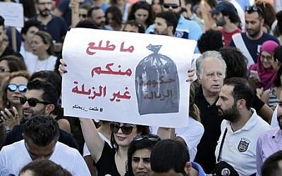 """Lebanese protesters chants slogans against the Lebanese government during a demonstration against the ongoing trash crisis, at the Martyrs square in downtown Beirut, Lebanon, August 8, 2015. The placard in Arabic reads: """"We got nothing from you but garbage."""" (AP Photo/Bilal Hussein)"""