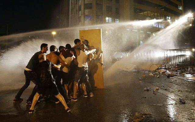 Lebanese activists shout anti-government slogans as they are sprayed by riot police using water cannons during a protest against the ongoing trash crisis, in downtown Beirut, Lebanon, Sunday, Aug. 23, 2015. (AP/Hassan Ammar)