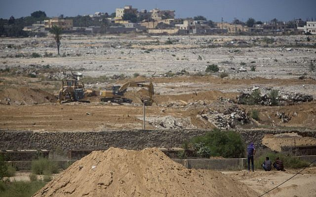 In this Sunday, Aug. 30, 2015 photo, bulldozers and diggers work at the Egyptian side of the border with Gaza Strip. (AP Photo/Khalil Hamra)