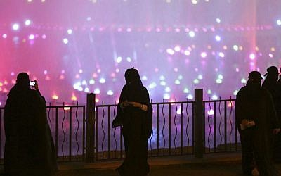 In this March 29, 2014, file photo, a Saudi woman takes photographs in a park during celebrations to mark the worldwide Earth Hour in Riyadh, Saudi Arabia. (AP/Hasan Jamali)