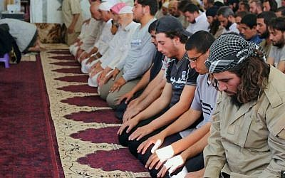 In this photo provided Friday, Aug. 7, 2015, by the Rased News Network, a Facebook page affiliated with Islamic State militants, Muslim worshipers attend Friday prayers in a mosque in the central Syrian town of Qaryatain. (Rased News Network, a Facebook page affiliated with Islamic State militants via AP)