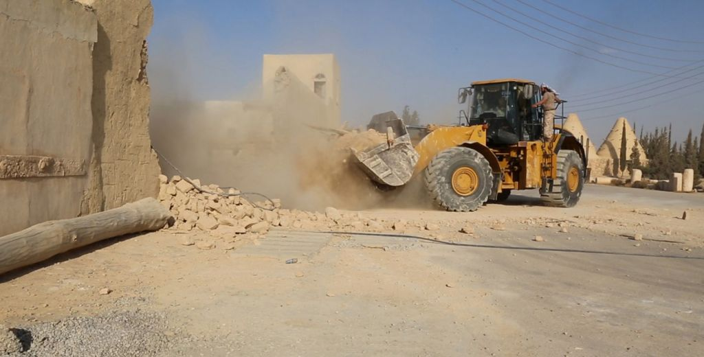 This picture released late Thursday, Aug. 20, 2015, by an Islamic State militant-affiliated website, shows a bulldozer of the Islamic State militants destroying the Saint Eliane Monastery near the town of Qaryatain which IS captured in early August, in Homs province, Syria. (Islamic State militant website via AP)