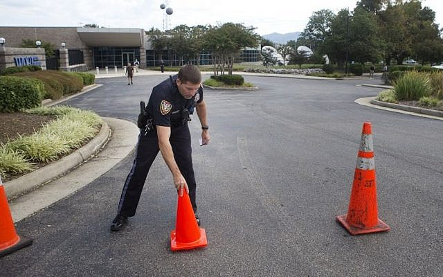 A Roanoke police officer moves road cones back into position after letting a vehicle through at WDBJ's Digital Broadcast Center, Wednesday, Aug. 26, 2015, in Roanoke, Va. (Erica Yoon/The Roanoke Times via AP)