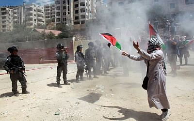 Palestinian protesters run for cover from tear gas shot by Israeli Border Policemen during clashes after a demonstration against the West Bank security fence in the mainly Christian village of Beit Jala, on August 30, 2015. (AFP/Musa al-Shaer)