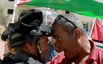 A Palestinian protester scuffles with an Israeli border policeman during during clashes following a demonstration against the West Bank security fence in the mainly Christian village of Beit Jala, on August 30, 2015. (Musa Al Shaer/ AFP)