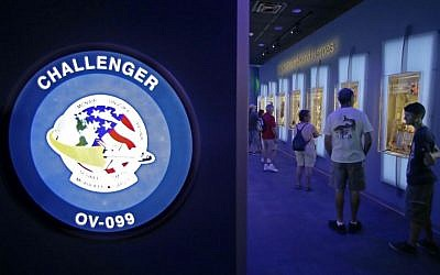 "In this Tuesday, July 21, 2015 photo, visitors look over display cases at the ""Forever Remembered"" exhibit and memorial for the astronauts that perished on the Columbia and Challenger space shuttles, at the Kennedy Space Center Visitor Complex in Cape Canaveral, Florida. (AP Photo/John Raoux)"