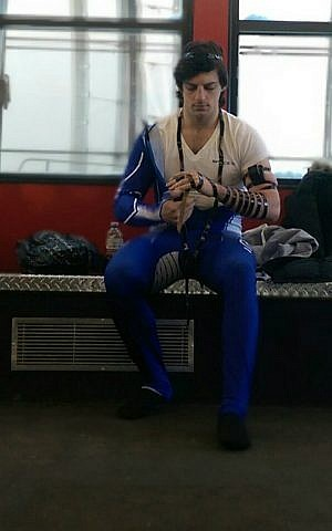 Self-described 'ambassador for all things Jewish' AJ Edelman prays with tefillin before a competition. (courtesy)