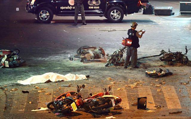 A policeman photographs debris from an explosion in central Bangkok, Thailand, Monday, Aug. 17, 2015. (AP Photo/Mark Baker)