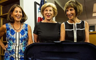 (Left to right) Amy Totenberg, Nina Totenberg and Jill Totenberg view their father's Stadivarius violin, which was stolen after a concert 35 years ago, at an FBI press conference in New York City announcing the recovery of the violin, on August 6, 2015. (Andrew Burton/Getty Images/JTA)
