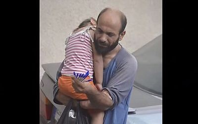 This image of Syrian-Palestinian refugee Adul Attar carrying his daughter while selling pens on the streets of Beirut went viral in August 2015, leading to donations of more than $116,000. (screen capture: YouTube)
