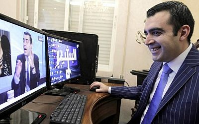 "Iraqi Ahmad al-Basheer, host of the ""Basheer Show"", watches a video of his TV show on a computer screen on July 29, 2015 at his studio in the Jordanian capital, Amman. (AFP PHOTO / KHALIL MAZRAAWI)"