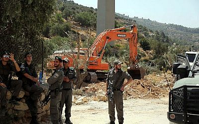 Israeli security forces stand guard as an Israeli excavator uproots olive trees to make way for the separation barrier, in the West Bank town of Beit Jala near the Jewish neighborhood of Gilo and the Palestinian town of Bethlehem on August 17, 2015. (Flash90)