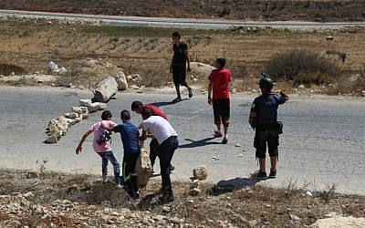 Palestinians use rocks to a close a street in Nabi Saleh during a protest (Eric Cortellessa/Times of Israel)