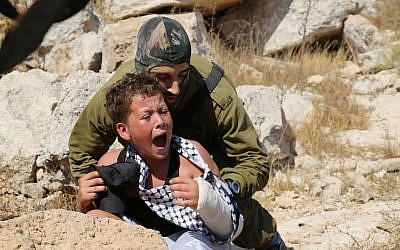An IDF soldier tries to arrest a 12-year-old boy, accused of stone throwing, at a demonstration in the West Bank village of Nabi Saleh on August 28, 2015 (Eric Cortellessa/ Times of Israel)