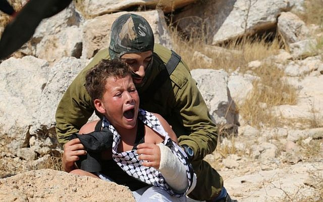 An IDF soldier tries to arrest a 12-year-old boy, accused of stone throwing, at a demonstration in the West Bank village of Nabi Saleh Eric Cortellessa/ Times of Israel)