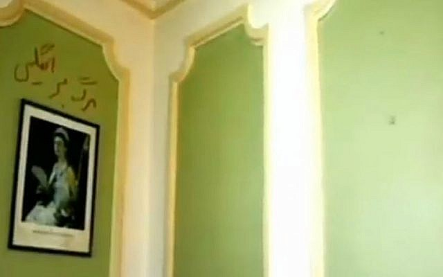 Four-year-old graffiti reading 'Death to England' is seen above a portrait of Queen Elizabeth II at the British embassy in Tehran as it reopened on August 23, 2015, for the first time since November 2011 riots. (screen capture: Channel 2)