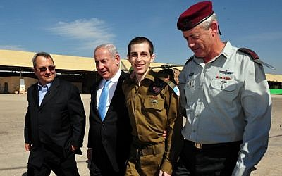 Released Israeli soldier Gilad Shalit (second right), walks with Prime Minister Benjamin Netanyahu (second left), then-defense minister Ehud Barak (left), and ex-chief of staff Lt. Gen. Benny Gantz (right), at the Tel Nof air base in southern Israel, October 18, 2011. (Ariel Hermoni/Defense Ministry/Flash90)