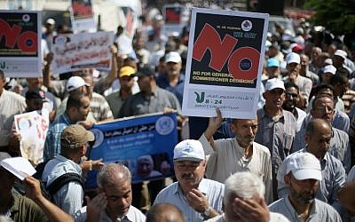 Palestinian employees of the United Nations hold placards during a protest against the reduction of educational programs given by the United Nations Relief and Works Agency (UNRWA) on August 24, 2015 outside the UNESCO headquarters in Gaza City. (AFP Photo/Mohammed Abed)