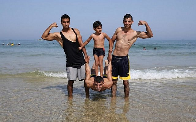 Members of Palestinian sports group Bar Palestine performing on the beach in Gaza, August 7, 2015 . (AFP/MOHAMMED ABED)