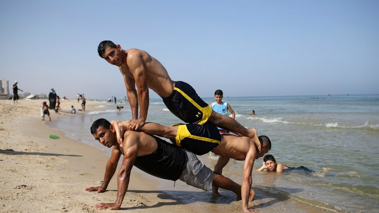 Members of Palestinian sports group Bar Palestine performing on the beach in Gaza City, August 7, 2015. (AFP/MOHAMMED ABED)