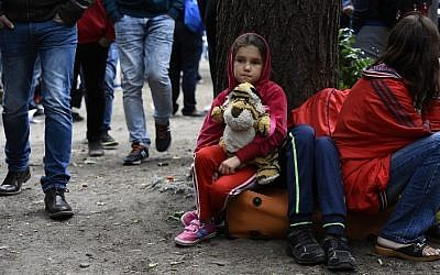Illustrative: A migrant child sits outside the State Office of Health and Social Affairs in Berlin (LAGeSo) where hundreds of migrants wait to receive help from the Berlin administration on August 25, 2015. (AFP Photo/Tobias Schwarz)