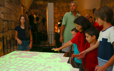 A group of visitors interacting with Ezri Tarazi's table, 'Remapping,' 2015. (Oded Antman)
