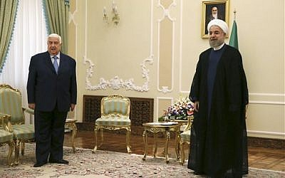 Hassan Rouhani, right, waited for the Syrian delegation as he was meeting with Syrian Foreign Minister Walid al-Moallem, left, at the presidency office in Tehran on Wednesday, Aug 5, 2015. (Vahid Salemi/ AP)