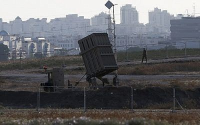 "An IDF soldier walks past an ""Iron Dome"" battery, a short-range missile defense system, designed to intercept and destroy incoming short-range rockets and artillery shells, on August 20, 2015, in the city of Ashdod. (AFP PHOTO / AHMAD GHARABLI)"