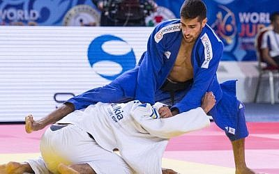 Golan Pollack (blue) competes with Ukraine's Georgii Zantaraia during the men's qualification match, in the -66kg category at the Judo World Championships in Astana on August 25, 2015. (AFP PHOTO / JACK GUEZ)