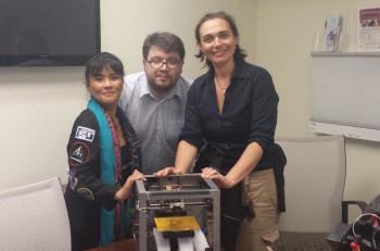 Gifford, right, looks over a 3D printer with scientists Dr. Susan Jewell and Matteo Borri. (Courtesy of Sheyna Gifford)