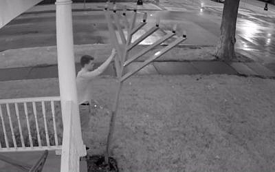 An image from security-camera footage released by the University of Illinois police, showing a man knocking over the campus menorah, August 21, 2015. (screen capture: YouTube)
